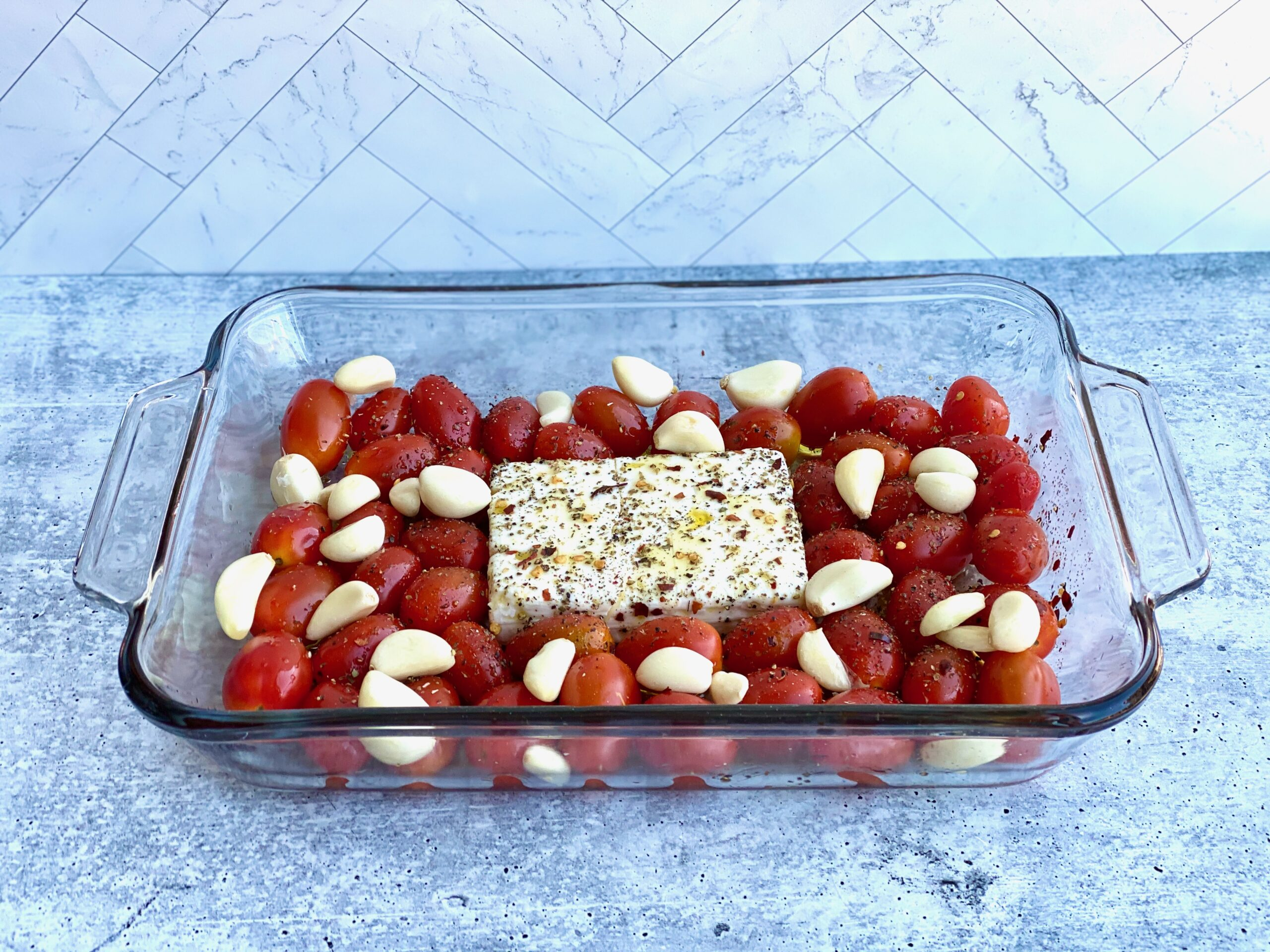 Image of feta cheese in a baking dish with tomatoes and whole cloves of garlic