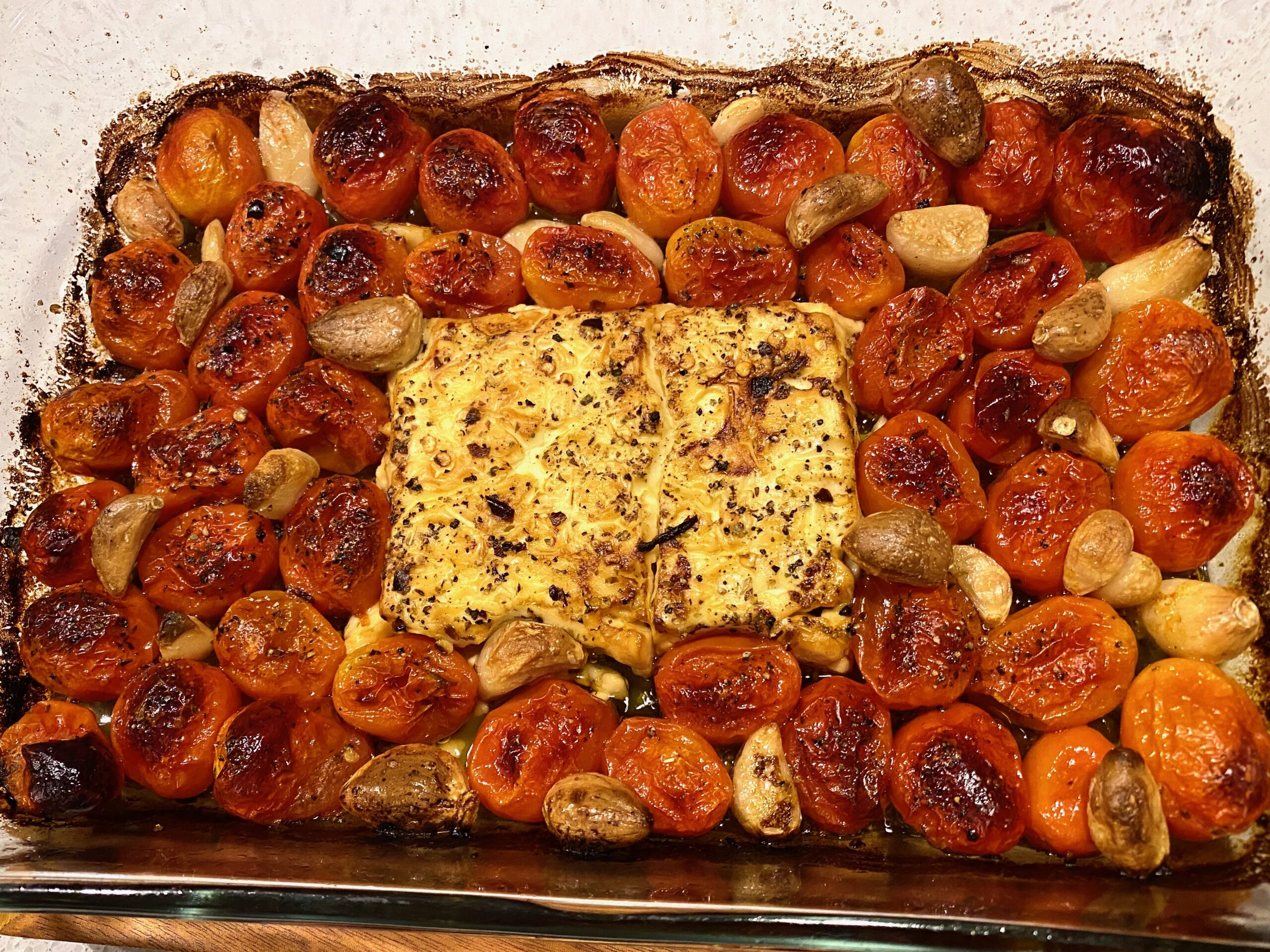 Image of a baking dish with golden brown baked feta and tomatoes