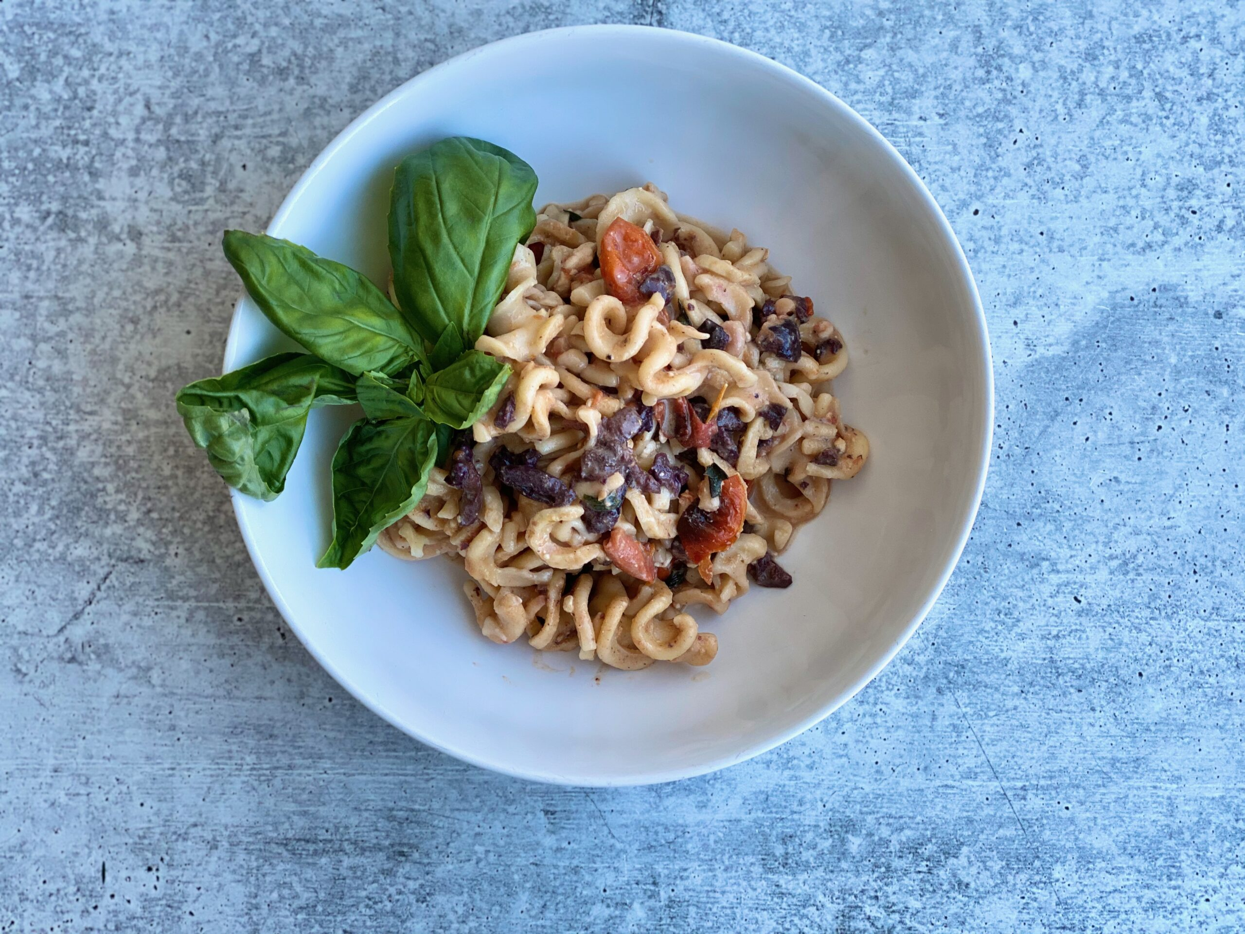 Image of pasta in a bowl with a basil garnish