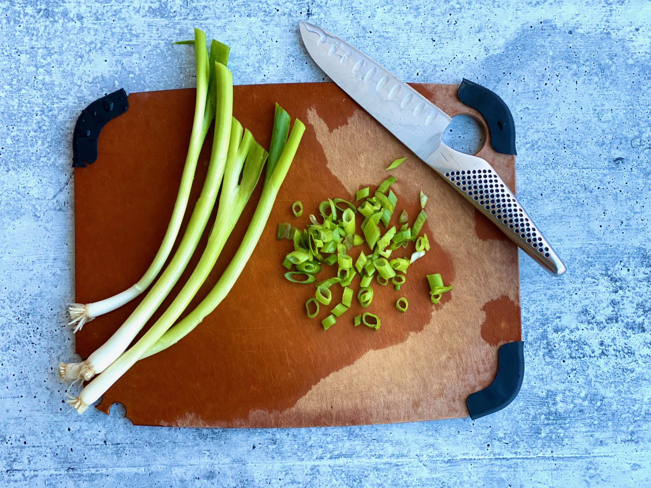 An image of scallions half chopped on a cutting board with a knife