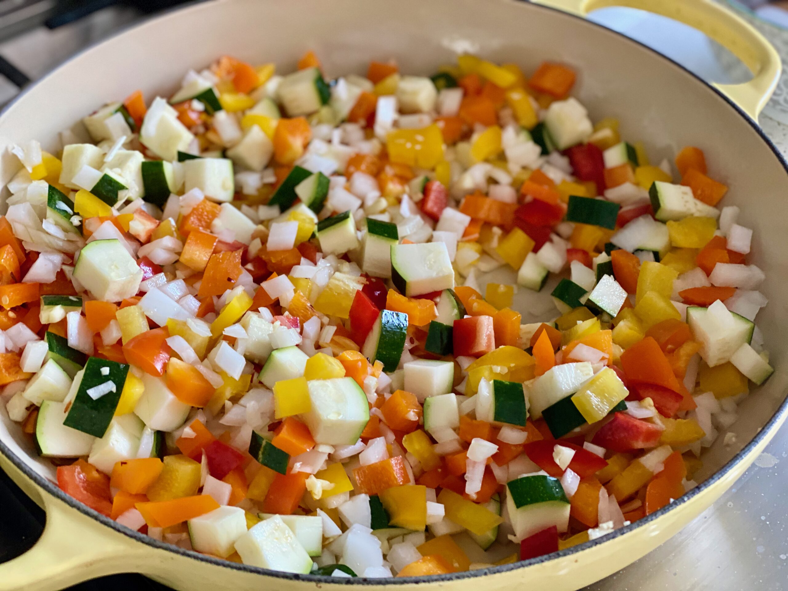 A pan of pepper, onions and zucchini cooking