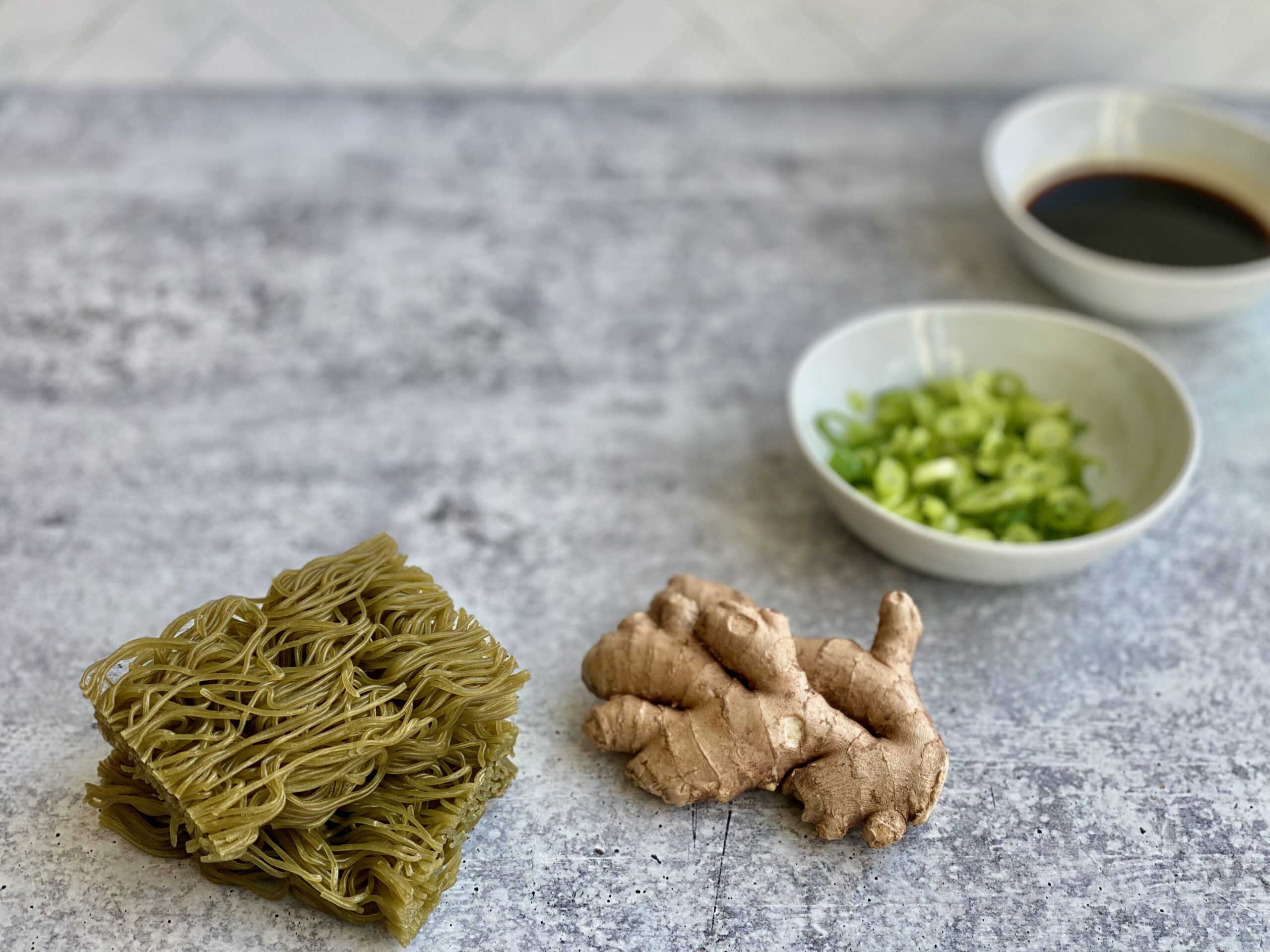 Image of ingredients to make ramen noodles including ginger, scallions and soy sauce.