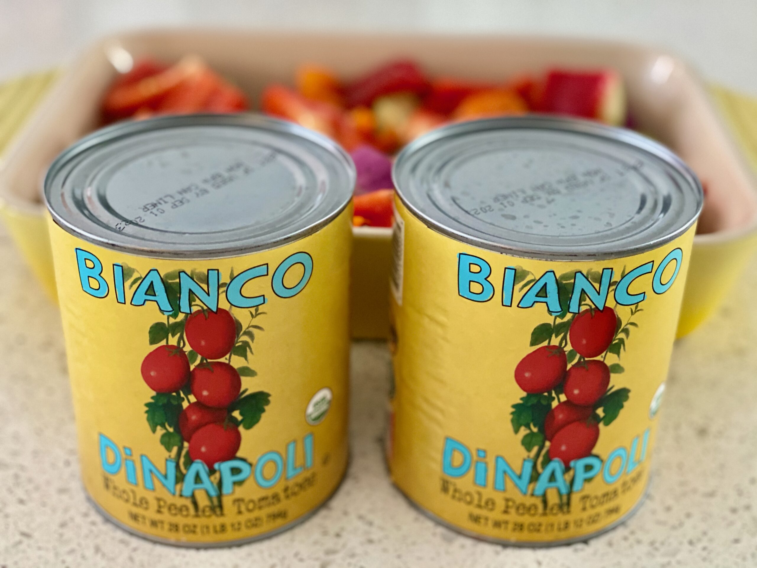An image of two cans of tomatoes with a pan of vegetables in the background