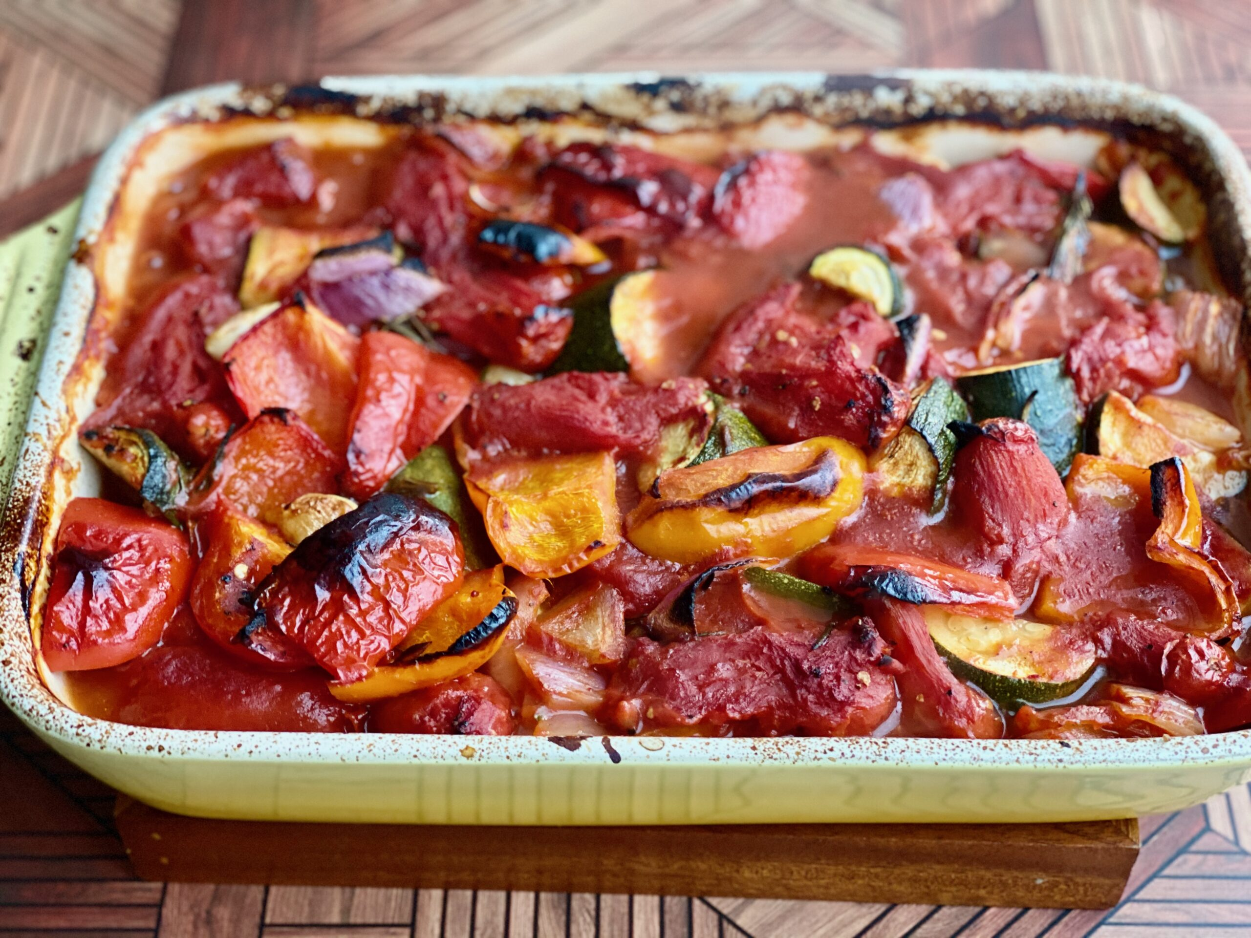 An image of a pan full of charred, roasted vegetables