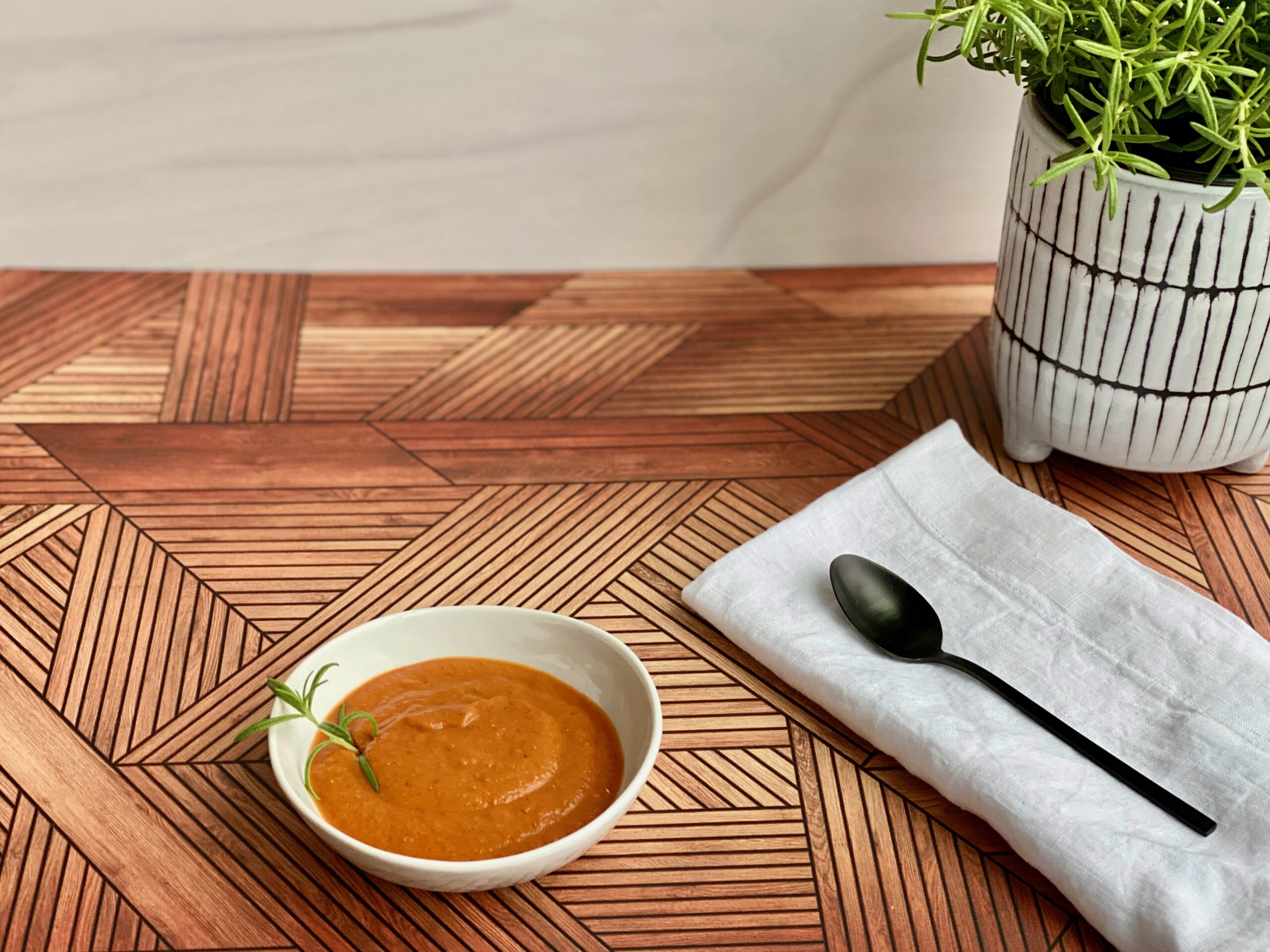 An image of a bowl of tomato soup with a rosemary plant in the background