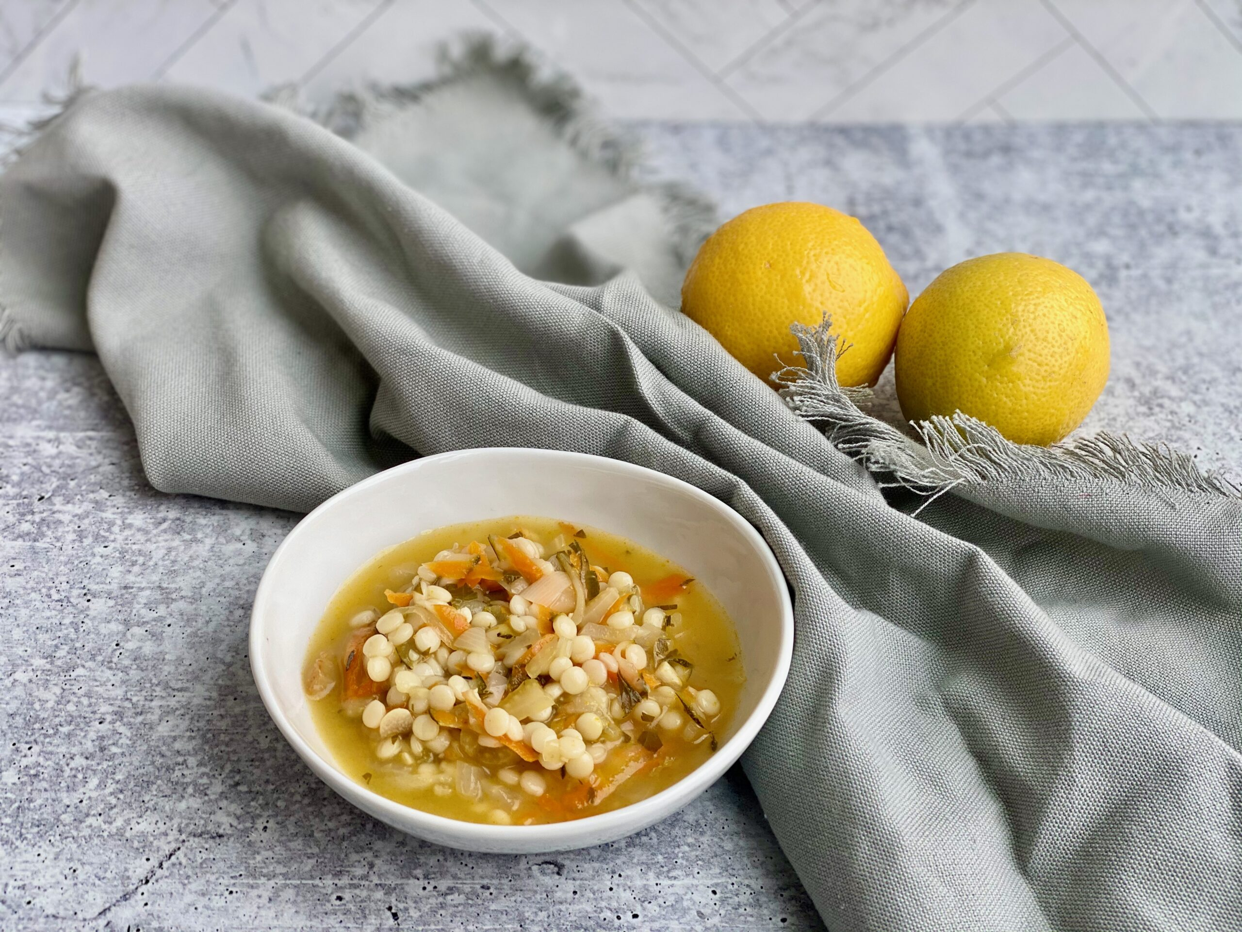 Picture of a bowl of soup with lemons in the background